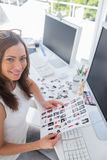 Smiling photo editor at work holding contact sheet Royalty Free Stock Photography