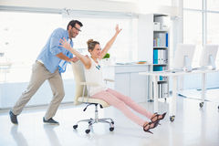 Smiling photo editors having fun with on a swivel chair Royalty Free Stock Image