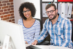 Smiling photo editors at office desk. Portrait of smiling photo editors sitting at office desk Royalty Free Stock Photography