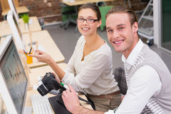 Smiling photo editors using computer in office Stock Image