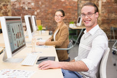 Smiling photo editors using computers in office. Portrait of smiling photo editors using computers in the office Stock Images
