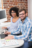 Smiling photo editors using digitizer in office Royalty Free Stock Photos