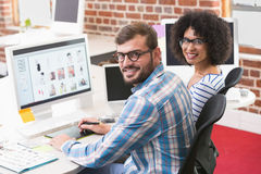 Smiling photo editors using digitizer in office. Portrait of smiling photo editors using digitizer in the office Royalty Free Stock Images