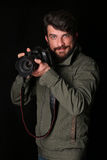 Smiling photographer with a camera. Close up. Black background Stock Images