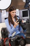 Smiling photographer checking camera Royalty Free Stock Photos