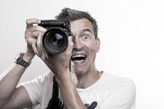 Smiling photographer. Photographer takes a vertical shot while laughing and smiling royalty free stock images