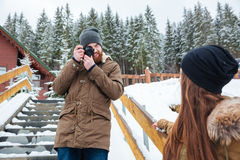 Smiling photographer taking photos of woman on stairs in winter Royalty Free Stock Photos