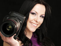 Smiling photographer woman. Smiling brunette photographer woman holding camera over dark background Stock Photo
