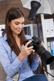Smiling photographer at work. Checking camera setting in studio Royalty Free Stock Photography