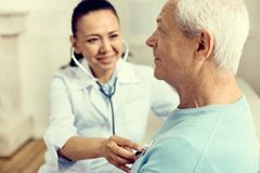 Smiling physician checking lungs of elderly man. Preventive measures. Selective focus on a positive minded retired gentleman attending his doctor and checking royalty free stock photo