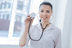 Smiling physician demonstrating professional device in the clinic Stock Images
