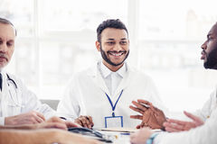 Smiling physician listening his colleagues at meeting Royalty Free Stock Photos