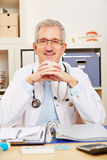 Smiling physician sitting at desk in office. Smiling old physician sitting at his desk in the office Stock Photo