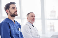 Smiling physicians looking report in hospital room Royalty Free Stock Image