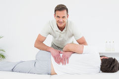 Smiling physiotherapist examining mans back Royalty Free Stock Images
