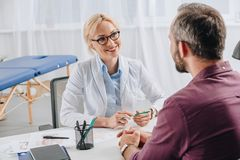smiling physiotherapist in white coat looking at patient during appointment