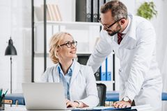 smiling physiotherapists in white coats looking at each other at workplace with laptop