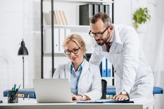 smiling physiotherapists in white coats using laptop together