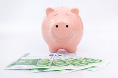 Smiling  Piggy bank with euro bills Royalty Free Stock Photo