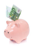 Smiling Piggy bank with euro bills Royalty Free Stock Photos