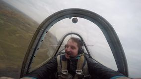 Smiling pilot sitting in the cockpit of a light aerobatic aircraft, emotions from the flight, aerobatics.  stock footage