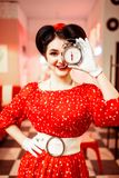 Smiling pin up girl posing with alarm clock,. Vintage cafe interior on background, popular american fashion 50s and 60s. Red dress with polka dots, bright make Royalty Free Stock Image