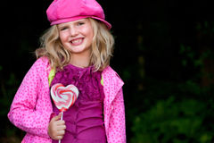Smiling pink girl with lolli Stock Photography