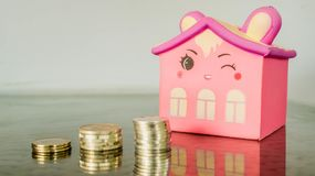 Smiling pink home figure and stack of coins. concept of house building,. Investment, loan, real estate, mortgage stock image
