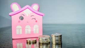 Smiling pink home figure and stack of coins. concept of house building,. Investment, loan, real estate, mortgage royalty free stock image