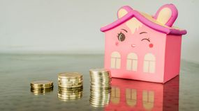 Smiling pink home figure and stack of coins. concept of house building,. Investment, loan, real estate, mortgage royalty free stock photo
