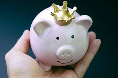 Smiling pink piggy bank wearing golden crown in man`s hand with Royalty Free Stock Photography