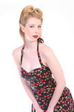 Smiling Pinup Girl. Pretty Blond Pinup Girl in a Rockabilly Cherry Stem Print Dress Stock Images