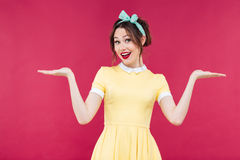 Smiling pinup girl in yellow dress holding copyspace on palms Royalty Free Stock Images