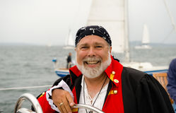 Smiling pirate skipper. At the helm of a sailboat on Elliot Bay, Puget Sound, Seattle, Washington Royalty Free Stock Photos