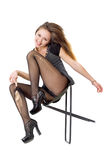 Smiling playful girl in the torn stockings. Sits on a chair royalty free stock photography