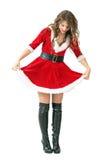 Smiling playful Santa girl lifting dress looking down. Stock Photo