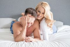 Smiling playful woman covering her husbands eyes Stock Photo