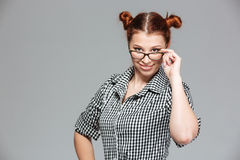 Smiling playful young woman looking over glasses Stock Photos