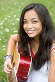 Smiling and playing guitar Stock Images