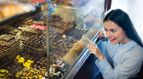 Smiling pleasant girl choosing delicious ganaches and chocolates Stock Images