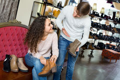 Smiling pleasant young couple buying winter shoes Royalty Free Stock Photography