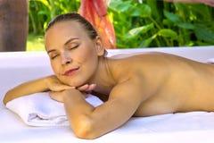 Smiling pleased female enjoys in spa. Stock Photos