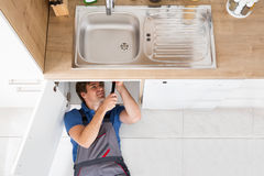 Smiling Plumber Fixing Sink Royalty Free Stock Photography