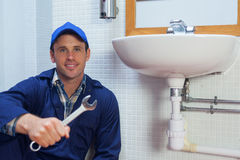 Smiling plumber holding wrench sitting next to sink Stock Images