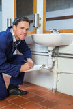 Smiling plumber inspecting sink holding clipboard Stock Photo