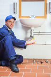 Smiling plumber repairing sink Royalty Free Stock Images