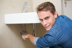 Smiling plumber repairing washbasin drain Stock Photography