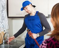Smiling plumber working at kitchen Stock Photography
