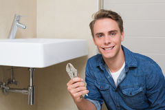 Smiling plumber with wrench by sink in bathroom Stock Images