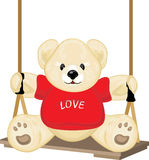 Smiling plush bear on the swing Royalty Free Stock Photo